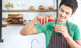 A portrait of handsome man making cold presses fruit juice in a modern kitchen. This beverage is extracted by juicer machine. Healthy lifestyle and weight loss stock image