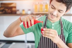 A portrait of handsome man making cold presses fruit juice in a modern kitchen. This beverage is extracted by juicer machine. Healthy lifestyle and weight loss stock photos