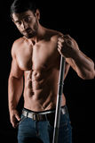 Portrait of a handsome man with muscular body. Holding barbell on black background Stock Images