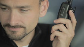 Portrait of handsome man with portable radio. Dispatcher controls the air-traffic in the control tower in airport. Commander is using the portable radio to give stock video footage