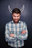 Portrait of handsome man pretending devil standing over chalkboard background Royalty Free Stock Photography