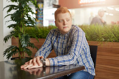 A portrait of a handsome man with red hair wearing checked shirt and jeans sitting at wooden table near green palm holding his han Royalty Free Stock Image