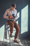 Portrait of handsome man with retro middle format camera in stud Royalty Free Stock Photography