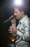 Portrait of handsome man singing on stage against spot light Royalty Free Stock Photography