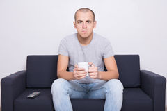 Portrait of handsome man sitting on sofa and watching tv with cu Royalty Free Stock Photography