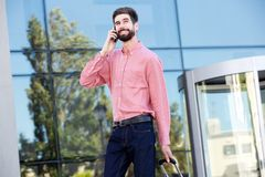 Handsome man smiling and talking on mobile phone outside Stock Images