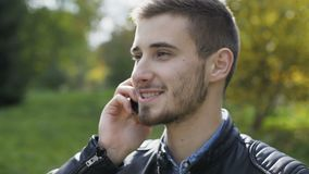 Portrait of handsome man speaking on a phone in autumn park 4K.  stock video footage
