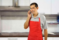 Speaking with phone at the kitchen Stock Images