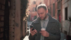 Portrait of Handsome man standing in the little street and using touchscreen technology at smartphone. Male spending time outdoors at morning stock video footage
