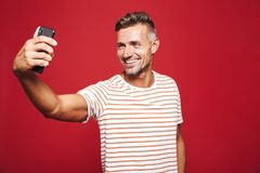 Portrait of a handsome man standing over red background stock image