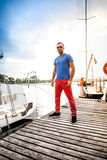 Portrait of handsome man standing on pier against white yachts Royalty Free Stock Photo