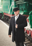 Portrait of handsome man in suit and bowler hat waiting for trai Royalty Free Stock Images