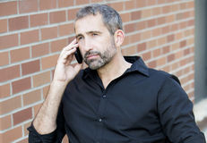 Portrait of handsome man talking on the phone. Portrait of handsome businessman talking on the phone outside Royalty Free Stock Images