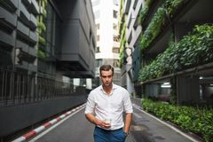 Portrait of a handsome man walking along a road royalty free stock image
