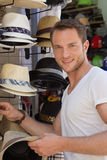 Portrait of handsome man wants to buy a summer hat. Royalty Free Stock Photo