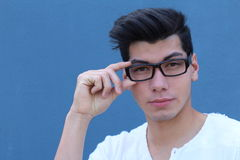 Portrait of handsome man wearing optical glasses isolated on blue. Young stylish Caucasian male model posing in studio Stock Photography