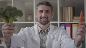 Portrait of handsome man in white robe looking in the camera proposing carrot and broccoli. Skillful doctor in modern. Portrait of handsome positive man in stock video