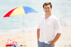 Portrait of handsome man in white short posing on beach Royalty Free Stock Photos
