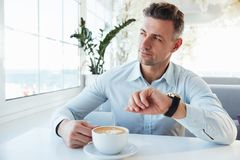 Portrait of handsome man with wrist watch on hand waiting for ap. Pointment in city cafe and drinking cappuccino Stock Image