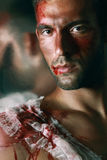 Portrait of handsome masculine bleeding man in jeans who prayin. Portrait of handsome masculine bleeding man with a Blood on his shoulder Face and lips wearing royalty free stock photography