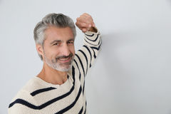 Portrait of handsome mature man with elbow on the wall. Portrait of handsome mature man on white background Royalty Free Stock Images