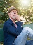Portrait of handsome mature man, light effect. Portrait of handsome mature man sitting on a bench, outdoors, light effect Stock Photos