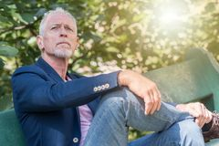 Portrait of handsome mature man, light effect. Portrait of handsome mature man sitting on a bench, outdoors, light effect Royalty Free Stock Image