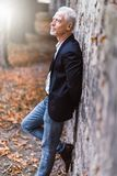 Portrait of handsome mature man, light effect. Portrait of handsome mature man standing against a wall, outdoors, light effect Royalty Free Stock Photos