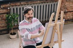 Mature Artist Painting in Art Studio. Portrait of handsome mature man painting sitting by easel in art class and smiling, enjoying work in spacious sunlit loft royalty free stock photography