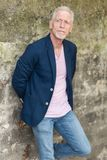 Portrait of handsome mature man. Standing against a wall, outdoors Royalty Free Stock Photo
