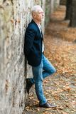 Portrait of handsome mature man. Standing against a wall, outdoors Royalty Free Stock Image