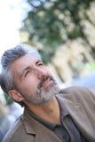 Portrait of handsome mature man on public bench Stock Photo