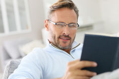Portrait of handsome mature man reading book Royalty Free Stock Photography
