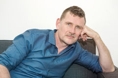 Portrait of handsome mature man sitting on couch royalty free stock images