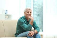 Portrait of handsome mature man on sofa stock photography