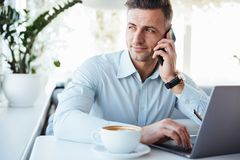 Portrait of a handsome mature man talking on mobile phone. Portrait of a handsome mature men talking on mobile phone and using laptop computer while sitting at stock photos