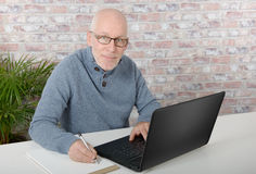 Portrait of a handsome mature man using laptop. At office Royalty Free Stock Photos