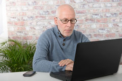 Portrait of a handsome mature man using laptop. At office Stock Photography