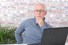 Portrait of a handsome mature man using laptop. At office Stock Photo