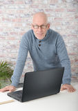 Portrait of a handsome mature man using laptop. At office Royalty Free Stock Photography