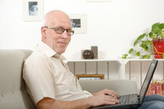 Portrait of a handsome mature man using laptop. On sofa Royalty Free Stock Image