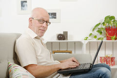 Portrait of a handsome mature man using laptop. On sofa Royalty Free Stock Photo