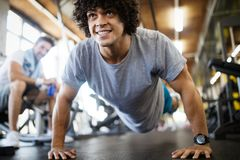 Portrait of a handsome man doing push ups exercise in gym. Portrait of a handsome men doing push ups exercise in fitness gym royalty free stock images