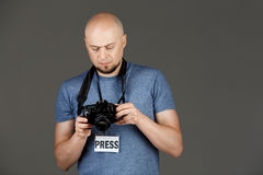 Portrait of handsome middle-aged man in grey shirt with photocamera and press badge taking pictures over dark background. Copy space Stock Photos