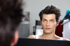 Portrait of handsome model at mirror in dressing room Stock Image