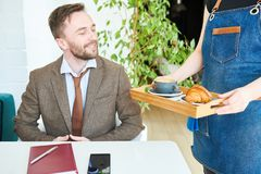 Businessman on Lunch Break in Cafe. Portrait of handsome modern businessman sitting at cafe table and smiling happily looking at unrecognizable waitress bringing Stock Photos
