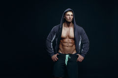 Portrait of a handsome muscular bodybuilder in hoodie posing ove Stock Photo