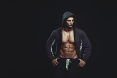 Portrait of a handsome muscular bodybuilder in hoodie posing ove Royalty Free Stock Photos