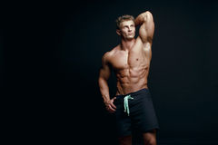 Portrait of a handsome muscular bodybuilder in hoodie posing ove Royalty Free Stock Image