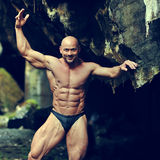Portrait of a handsome muscular bodybuilder posing in a cave Stock Photo